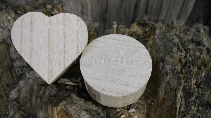 Wooden closed boxes in the shape of a heart and circle on stump stock image