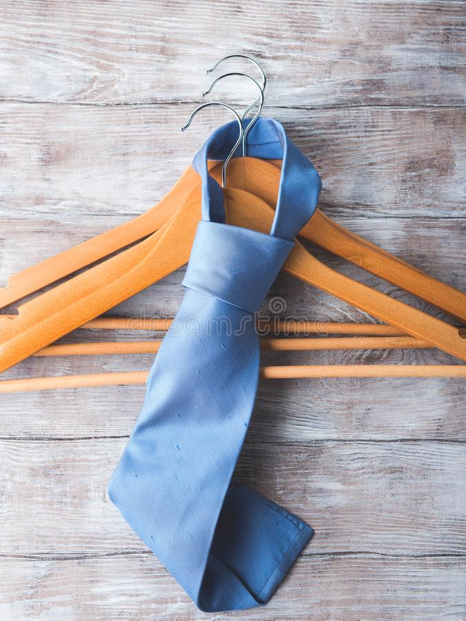 Wooden clothes hangers with man`s tie. Wooden clothes hangers with man`s elegant blue tie on wooden background. What nothing to wear concept. Men clothing royalty free stock image