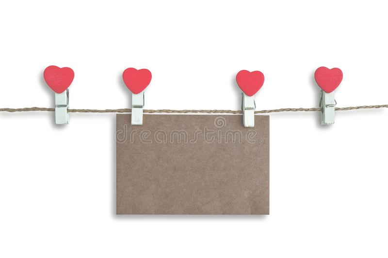 Wooden clothespin with heart shape design and brown paper sheet for valentine concept isolated. On white background stock photography