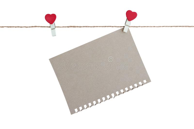 Wooden clothespin with heart shape design and brown paper sheet for valentine concept isolated. On white background royalty free stock photography