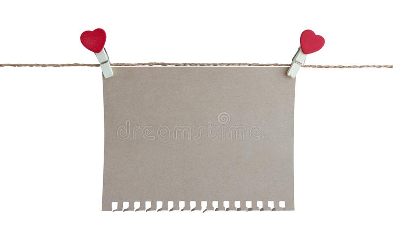 Wooden clothespin with heart shape design and brown paper sheet for valentine concept isolated. On white background stock photo