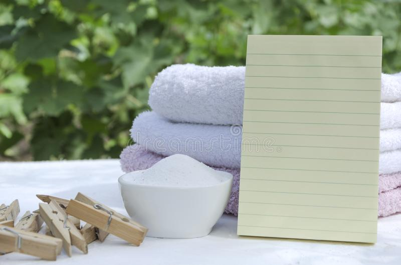 Wooden clothespins, bowl of laundry powder, stack of clean towels and blank  cleaning list. Laundry powder, clean towels on the white surface.Natural ligth stock photography
