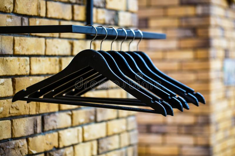 Wooden coat hanger clothes. Fashionable different types of hanger. Wood Hangers coat. Many wooden black hangers on a rod stock photos