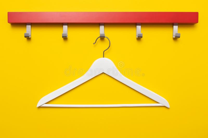 Wooden coat hanger or clothes hanger on a colored background stock photo