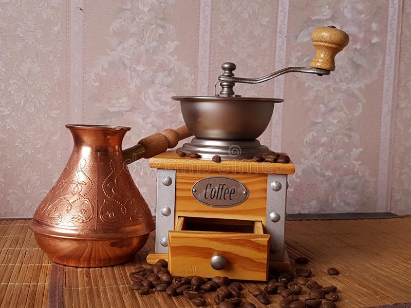 Wooden coffee grinder and cezve on the table royalty free stock photography