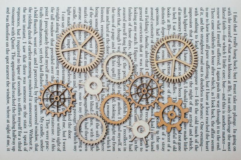 Wooden cogwheels on a book. Industry concept information. Wooden cogwheels on a page of a book. Industry concept information royalty free stock photos