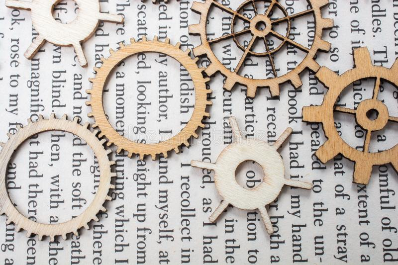 Wooden cogwheels on a book. Industry concept information. Wooden cogwheels on a page of a book. Industry concept information stock photo