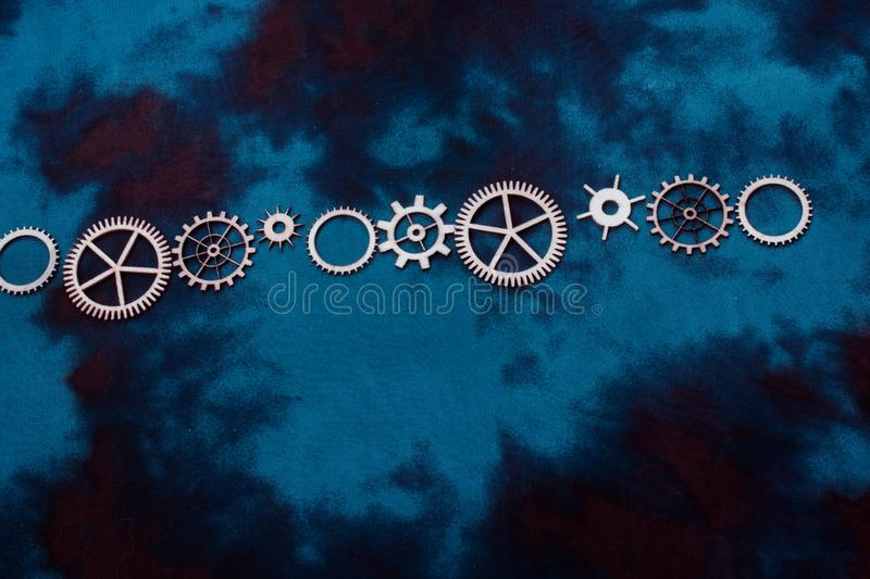 Wooden cogwheels on a fabric as cogwheels industry mechanism. Wooden cogwheels on a fabric industry concept information royalty free stock photos