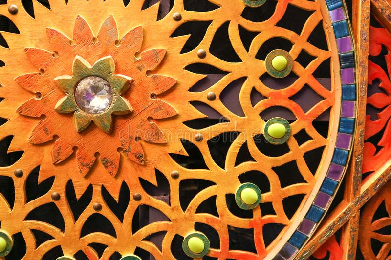 Wooden, colored, bright, mottled carved wall with flowers, stars, patterns, colored stones of different shapes and sizes and a dia stock image