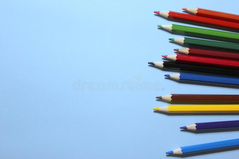 Wooden colored pencils on blue background artist`s tools stock photography