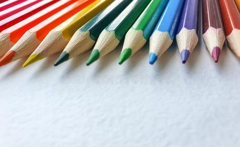 Wooden colored pencils, rainbow style, on the white sheet of drawing paper with specific texture. Copy space for text royalty free stock photography