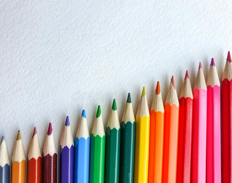 Wooden colored pencils, rainbow style, on the white sheet of drawing paper with specific texture. Copy space for text royalty free stock images