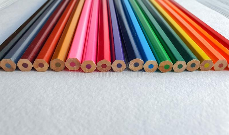 Wooden colored pencils, rainbow style, on the white sheet of drawing paper with specific texture. Copy space for text stock image
