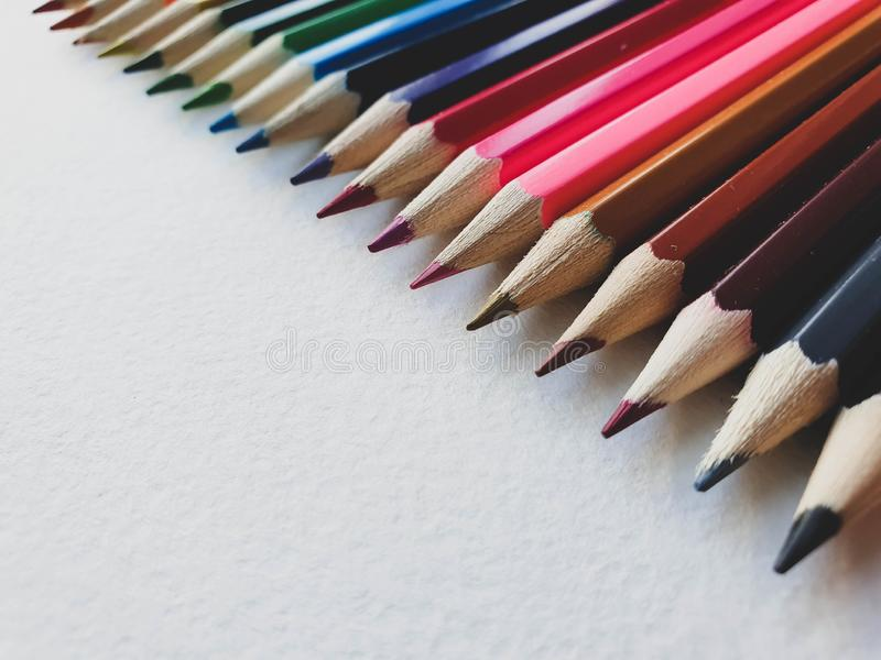 Wooden colored pencils, rainbow style, on the white sheet of drawing paper with specific texture. Copy space for text royalty free stock photo