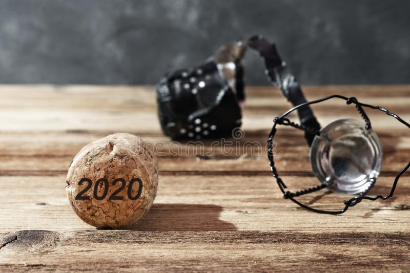 Wooden cork and champagne cap on brown background with date 2020. New year celebration concept.  stock images