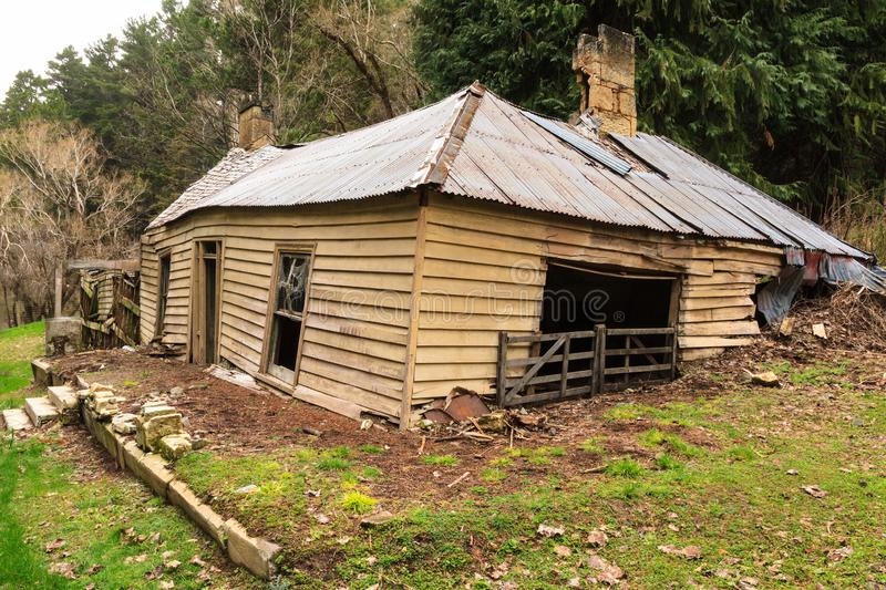 An old abandoned farmhouse collapsing into the earth. This wooden and corrugated iron farmhouse, built a hundred years ago and unused for decades, is sagging and royalty free stock image