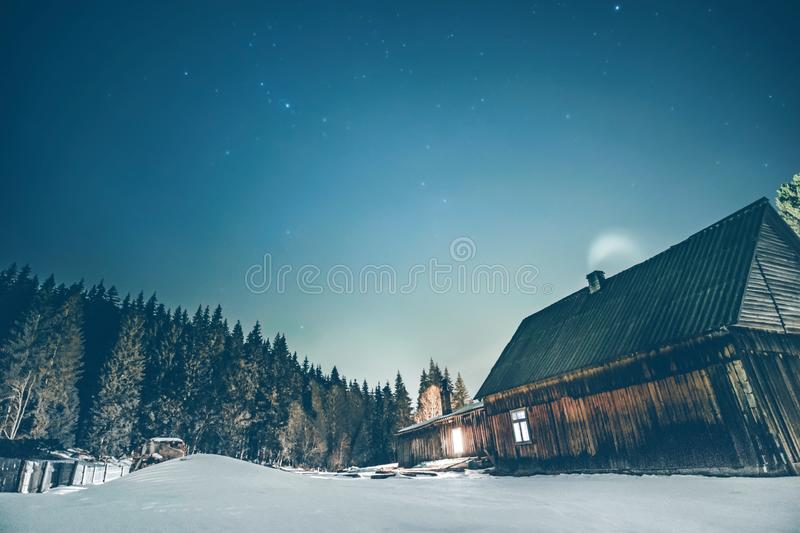 Wooden cottage with blue starry sky at night. Rural wooden cottage in the mountains with windows glowing in the dark at winter night. Wooden hut on hill moutains royalty free stock photography