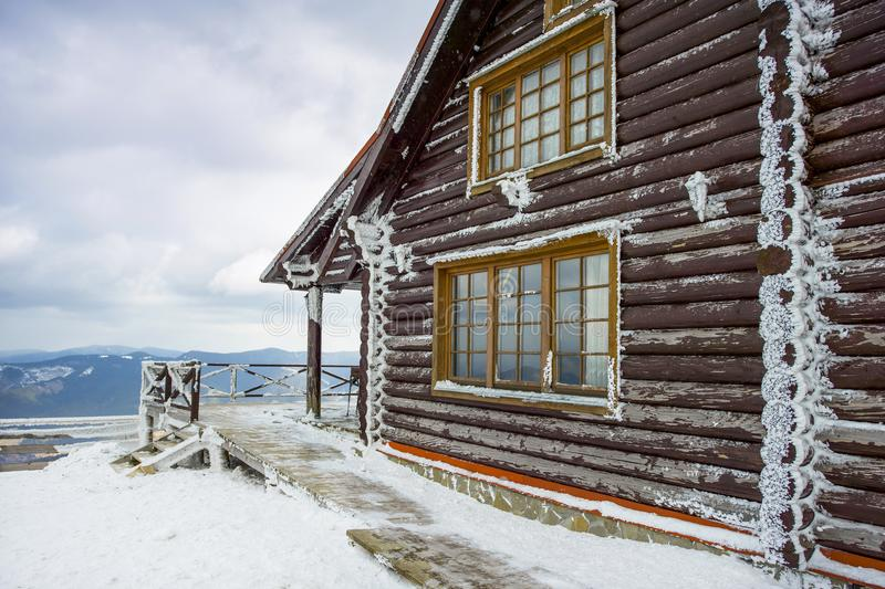 Wooden cottage chalets in the mountains. Bukovel, Ukraine - 29 November 2017: Wooden cottage chalets in the mountains, winter landscape of the Carpathian royalty free stock images