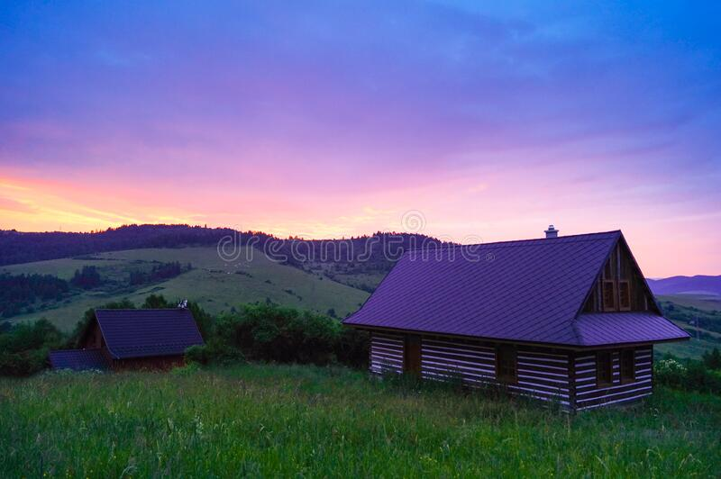 Wooden cottage in field at sunset royalty free stock photos