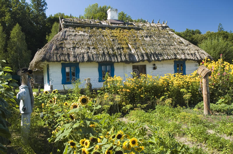 Wooden cottage house and a garden stock images