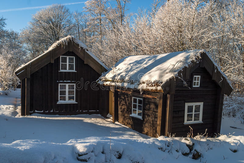 Wooden cottages in winter landscape royalty free stock photo