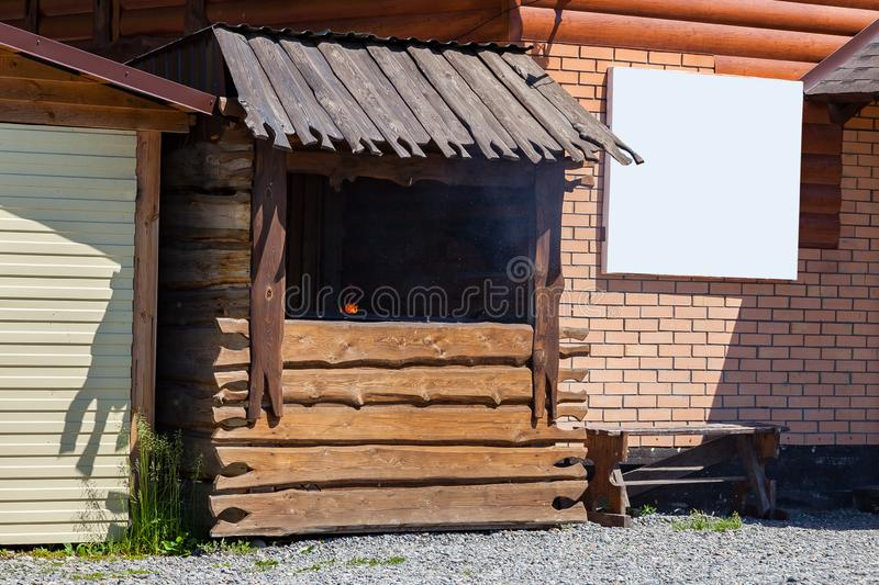 Wooden counter for cooking roasted meat with a barbecue grill, barbecue and a burning fire from royalty free stock images