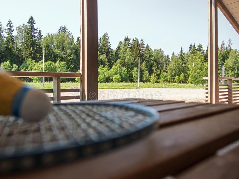 Wooden country furniture on the terrace of a country house. Blurred badminton racket and shuttlecock on wooden table. Lush green. Foliage in the background in royalty free stock photos