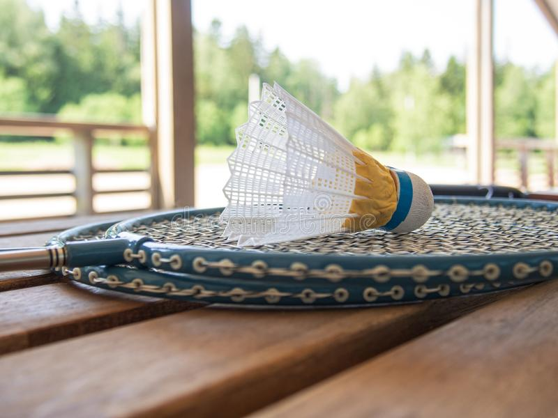Wooden country furniture on the terrace of a country house. Two badminton rackets and shuttlecock lie on a wooden table. Lush. Green foliage in the background royalty free stock photo