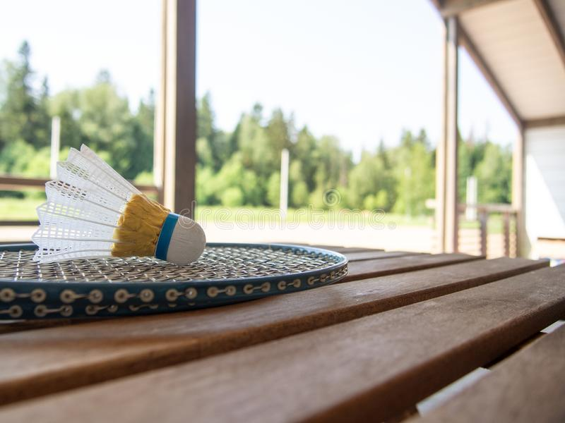 Wooden country furniture on the terrace of a country house. Two badminton rackets and shuttlecock on wooden table. Lush green. Foliage in the background is royalty free stock photo