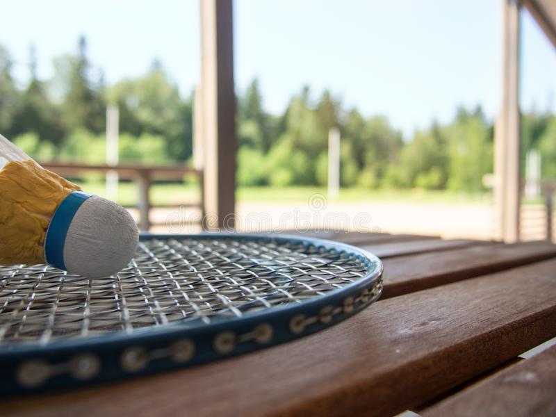 Wooden country furniture on the terrace of a country house. Badminton racket and shuttlecock on wooden table. Lush green foliage. In the background is blurred royalty free stock photos