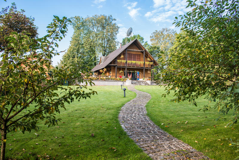 Wooden country house. Wooden, beautiful country house with stone path or road, trees and blue sky stock photo
