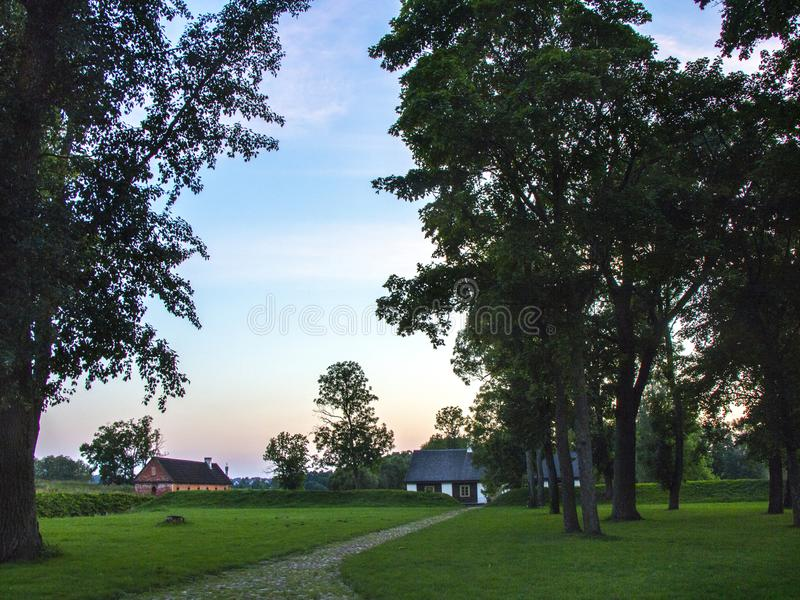 Wooden country house in the summer evening landscape. Lithuania royalty free stock photos