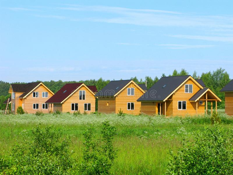 Wooden country houses on green field, eco construction royalty free stock image
