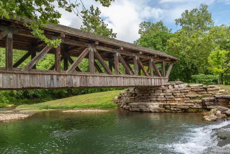 Wooden covered bridge over stream in canyon park. With summer foliage stock images