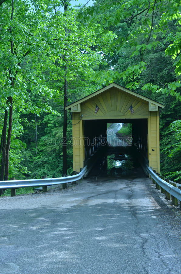 Wooden covered bridge on rural road in Ohio, USA. Wooden covered bridge built in 1867 in the Town Lattice style sits atop cut stone abutments and is a single stock photography