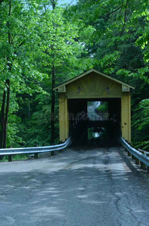 Wooden covered bridge on rural road in Ohio, USA. Wooden covered bridge built in 1867 in the Town Lattice style sits atop cut stone abutments and is a single stock photos