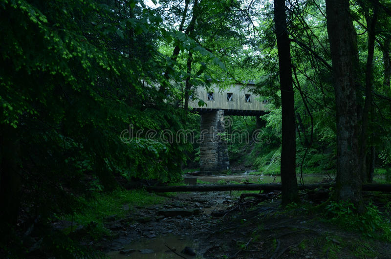 Wooden covered bridge on rural road in Ohio, USA. Wooden covered bridge built in 1867 in the Town Lattice style sits atop cut stone abutments and is a single royalty free stock images
