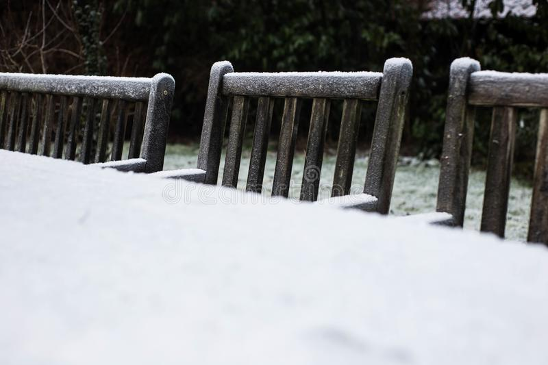 Wooden cozy garden chairs covered in snow in a backyard garden. stock photo