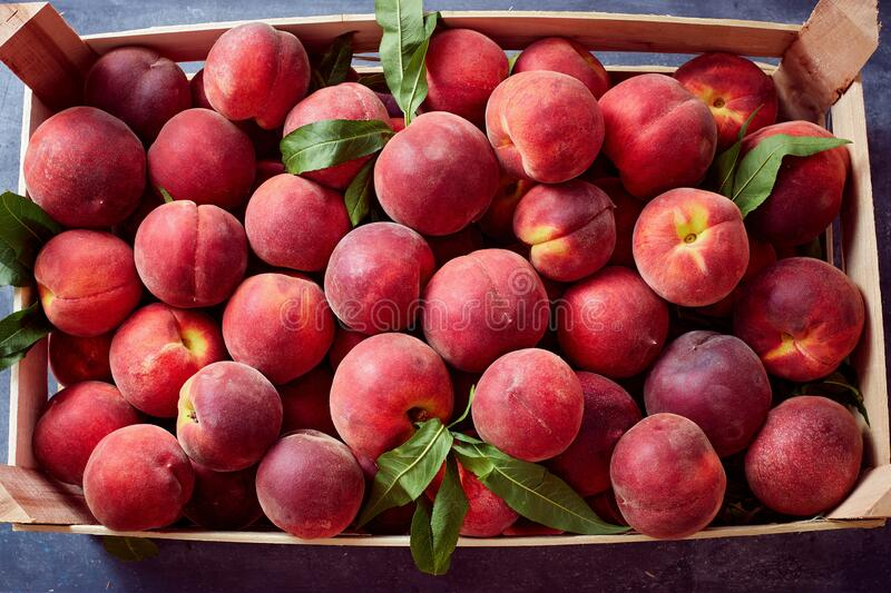 Wooden crate with fresh sweet peaches royalty free stock photos
