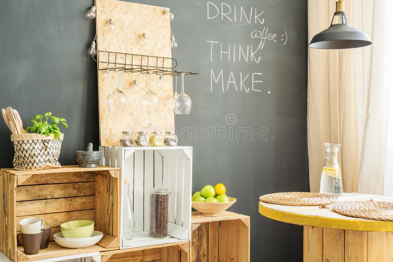 Wooden crates in kitchen. Wooden crates and table in modern kitchen with blackboard wall royalty free stock photos
