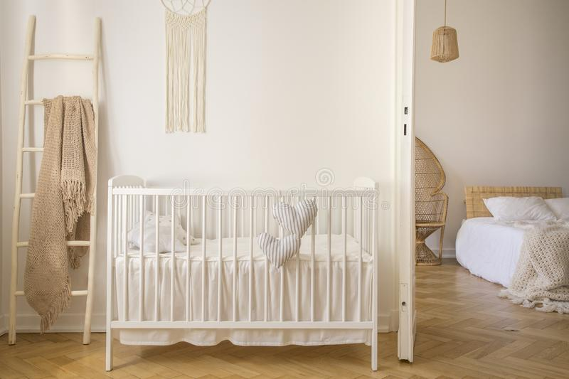Wooden crib with cushions standing in real photo of white kid room interior with blanket on ladder. And macrame on the wall stock photos