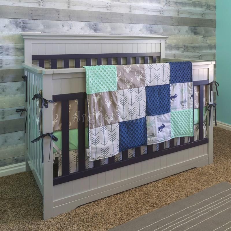 Wooden crib draped with quilt. Inside a nursery. Quilt with a deer and arrow design is draped on a white and dark blue wooden crib. The nursery has grey, white stock image