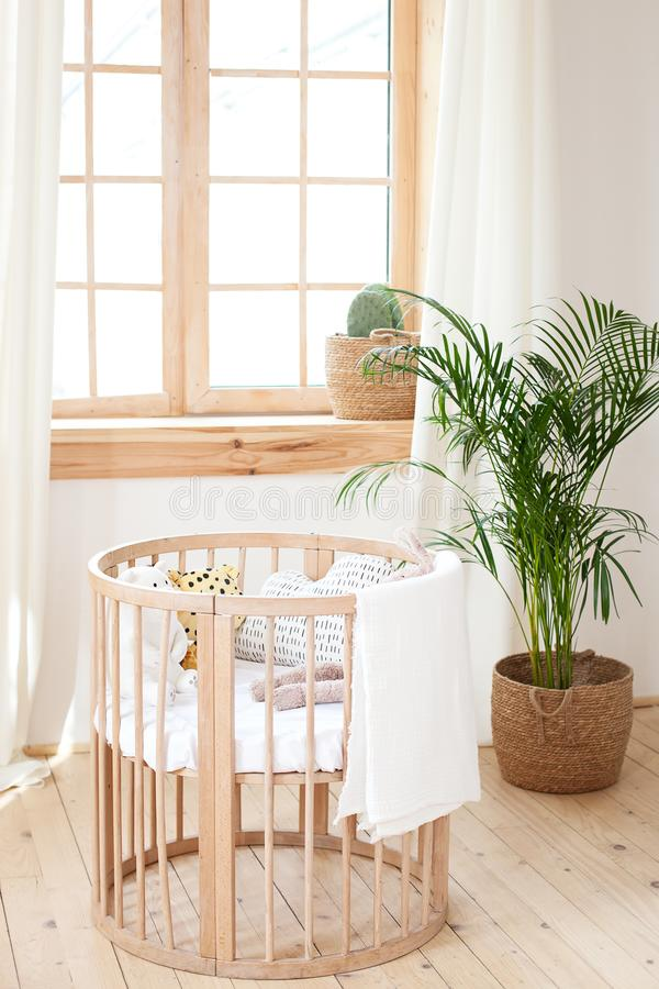 Wooden crib in an environmentally friendly cozy interior. Light brown children bedroom with a wooden empty crib. Cozy house Hygge royalty free stock photos