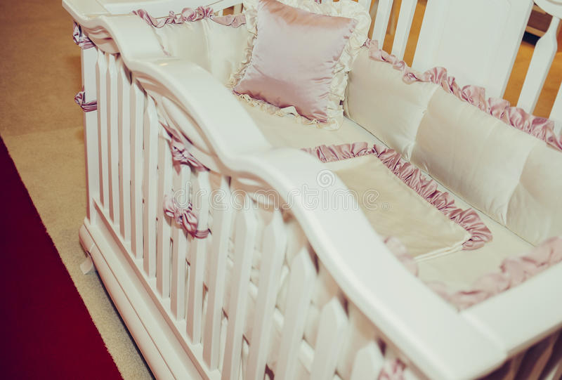 Wooden crib and retro silk bedding and pillows royalty free stock photo
