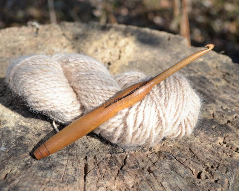 Wooden crochet hook and yarn. A handmade wood crochet hook displayed with a handspun skein of white wool yarn stock photography