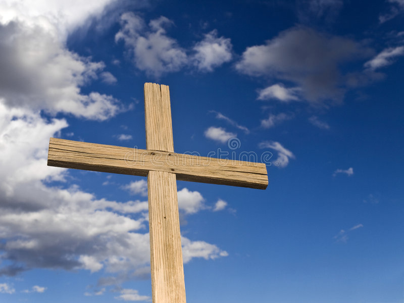 Wooden cross. A wooden cross over a blue sky with clouds royalty free stock photos