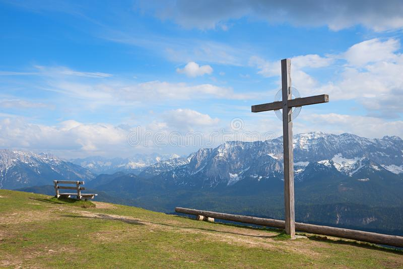 Wooden cross and bench at wank mountain summit. With view to the bavarian alps stock photo
