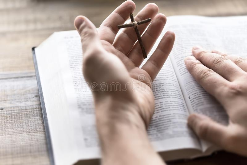 Reading Holy Bible holding a wooden cross in hand. Wooden cross and bible in hand. The way to God through prayer. The hope of salvation. Life-giving light in the stock image
