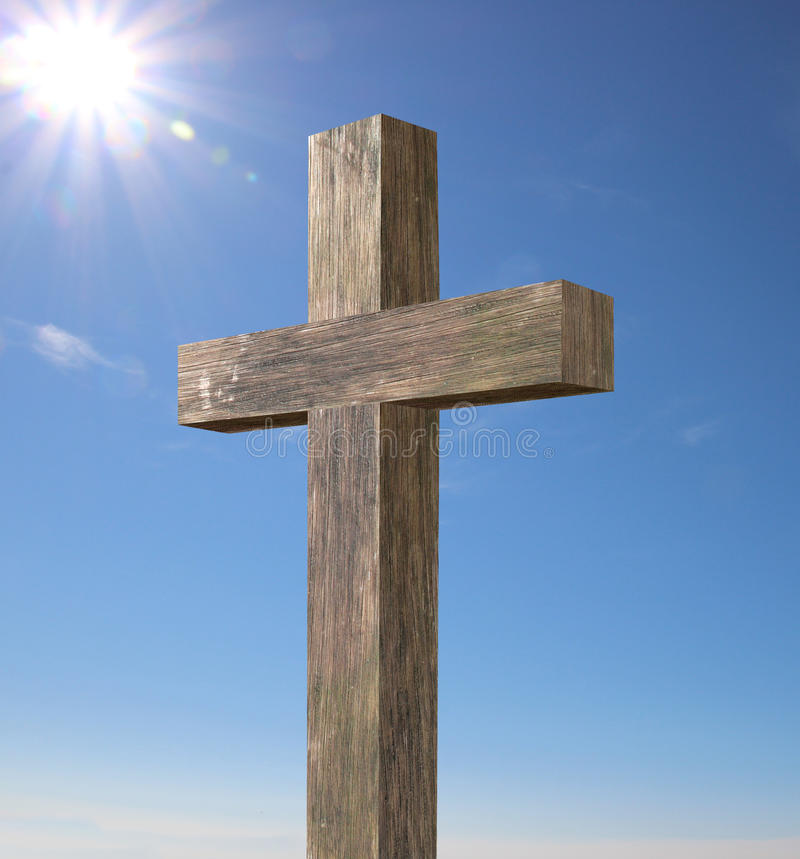 Wooden cross. In front of blue sky and sun rays stock image