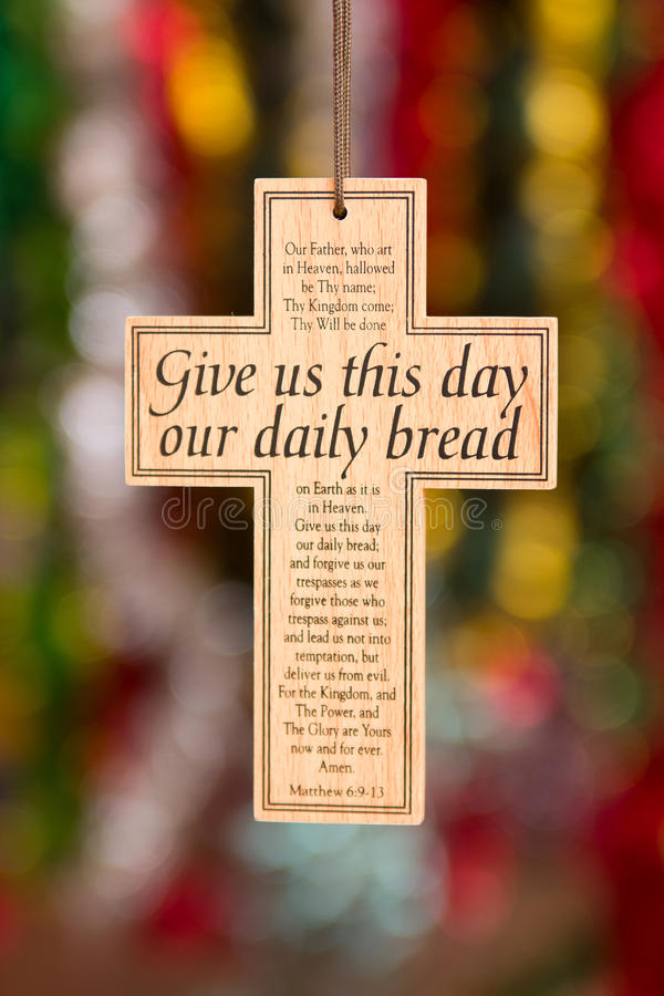 Wooden cross. With Give us this day our daily bread and words of prayer written across it stock images